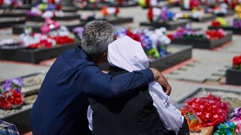27.04.2018, Kosovo, Meja: Ein Mann hält bei einer Zeremonie am jährlichen Gedenktag für die Vermissten im Kosovo vor den Gräbern im sogenannten «Tal der Trauer», wo vor 19 Jahren 376 albanische Zivilisten von der serbischen Armee getötet wurden, eine Frau im Arm.