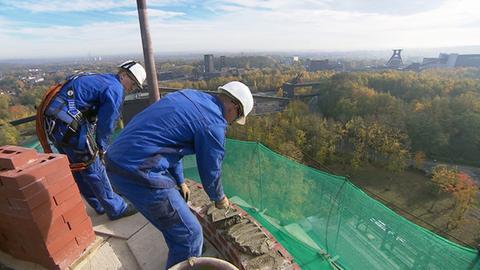 Männer arbeiten auf einem Schornstein