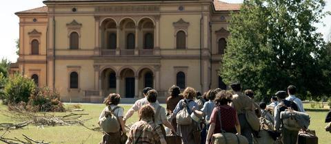 Kinder und Jugendliche laufen auf eine Villa zu.