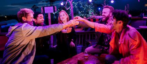 """Szenenfoto aus ARD-Serie """"All you need"""", junge diverse Menschen feiern gemeinsam draußen, Sommerabend, sitzen an einem Tisch"""