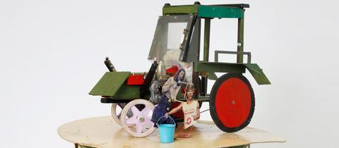 Traktor aus Holz gefertigt, davor zwei hölzerne Figuren - eine Installation des Frankfurter Künstlers Marko Lehanka (2011), Preisträger des Marielies-Hess-Kunstpreises 2019