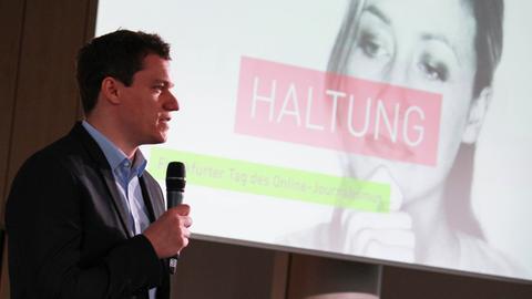 """Moderator mit Mikrofon in der Hand vor einer Leinwand mit dem Schriftzug """"Haltung"""""""