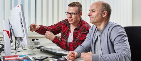 Auszubildender und Ausbilder besprechen sich am PC