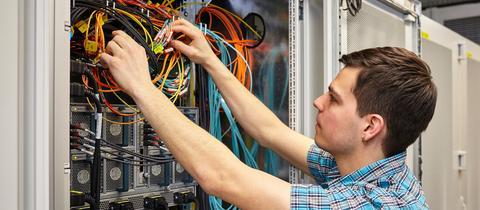 Auszubildender steckt Kabel zusammen