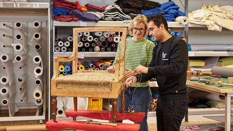 Auszubildender und Ausbilderin arbeiten an einem Stuhl