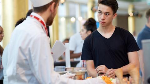Koch und Schüler sprechen miteinander