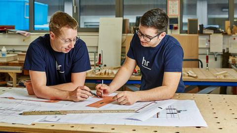 Ausbilder und Auszubildender planen einen Holzzuschnitt