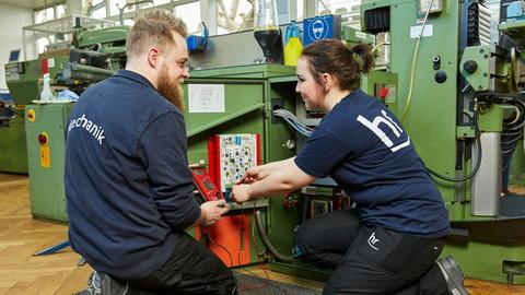 Auszubildende und Ausbilder in der Mechanik arbeiten an einer Maschine