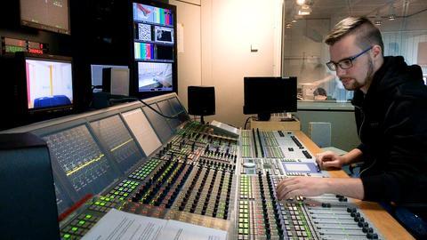 Auszubildender Mediengestalter sitzt im Studio am Mischpult