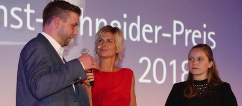 Julian Herbst, die Moderatorin der Verleihung Barbara Hahlweg und Anja Lordieck stehen auf der Bühne
