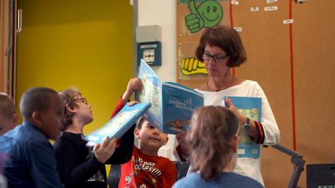 Petra Bollmann steht umringt von Grundschülern im Klassenraum.
