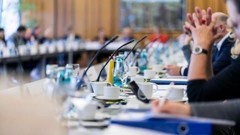 Blick in einen Konferenzsaal, in dem der hr-Rundfunkrat tagt. Das Bild ist weichgezeichnet, so dass die Situation nur schemenhaft erkannt werden kann.