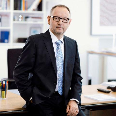 Manfred Krupp steht im Anzug vor seinem Schreibtisch
