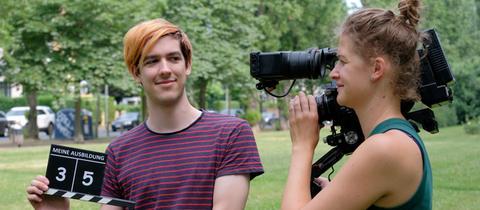 """Motivbild für die hr-Aktion """"Meine Ausbildung - Du führst Regie"""": Zwei Schüler*innen mit Filmkamera und Filmklappe"""