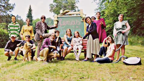 Schüler, Schülerinnen und Lehrer des Drachenschule Odenwald in Wald-Michelbach posieren im Freien vor einer Schultafel