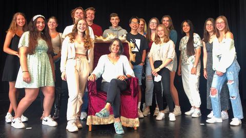 Schüler und Schülerinnen stehen auf einer Bühne und ihre Lehrerin sitz in der Mitte auf einem thronartigen Sessel