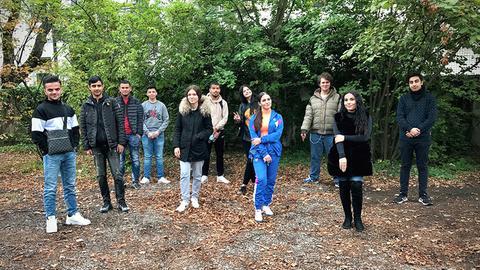 Schüler und Schülerinnen der Klingerschule in Frankfurt stehen im Park und lächeln in die Kamera