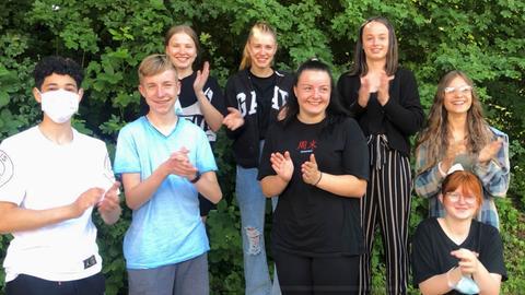 Schüler und Schülerinnen der Leo-Sternberg-Schule in Limburg stehen im Freien und freuen sich