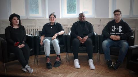Drei Schülerinnen und ein Schüler sitzen in einem Raum und lächeln in die Kamera