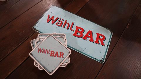 """Bildmarke zu """"WählBAR – Theken-Talk zur Bundestagswahl"""". Ein Metallschild und Bierdeckel, bedruckt mit dem Begriff Wählbar, liegen auf einem Holztisch."""
