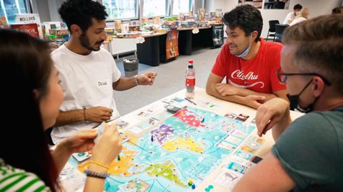 Eine Gruppe bestehend aus einer Frau und drei Männern spielen ein Board Game