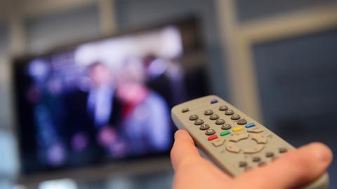 Eine Fernbedienung wird Richtung Fernseher gehalten.