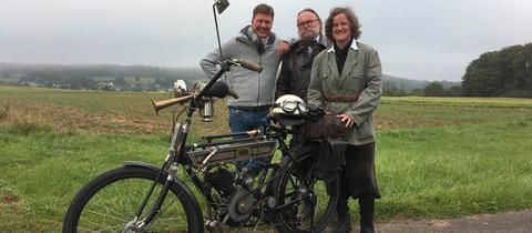 Moderator Dieter Voss (links) mit Baldur und Lian Klaas, die motorisierte Zweiräder aus der Zeit um 1900 sammeln.