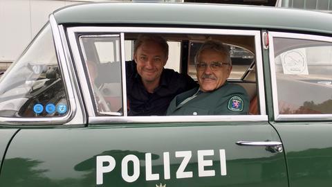 In einem Museumsstück aus dem Deutschen Polizeioldtimer-Museum in Marburg: Moderator Tobias Kämmerer (links) mit dem Polizei-Pressesprecher Eberhard Dersch