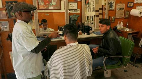 """Bob (links) und Florian (rechts) mit einem Kunden in Bobs """"Hairbase"""""""