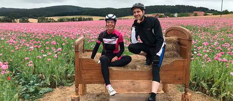Petra Schildwächter und Danny Morgenstern vor einem Mohnfeld auf dem Hohen Meißner
