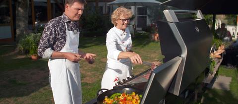 Moderator Dieter Voss steht mit Hannelore Mayer-Stahl an einem Grill