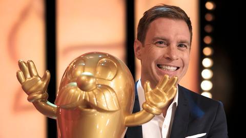 """Jens Kölker mit der """"Dollen Dorf""""-Trophäe, dem """"Goldenen Onkel Otto"""""""
