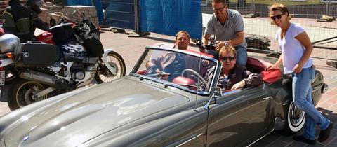 Tobias Kämmerer sitzt mit G.G. Anderson, Kameramann Lukas Lowack und Tonfrau Simone Jung in einem Auto.