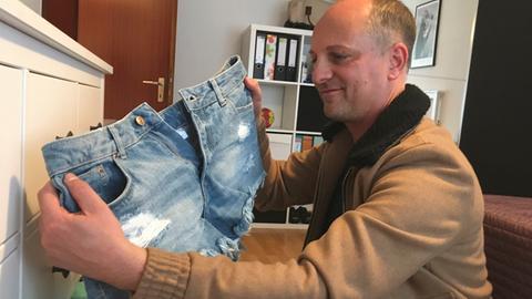 Der Kandidat hält eine Jeanshose in der Hand