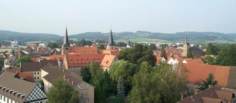 Blick auf Schlüchtern. Im Vordergrund der Klosterkomplex mit den beiden Klostertürmen. Rechts der Kirchturm der Stadtkirche St. Michael. Die drei Türme sind das Wahrzeichen der Stadt