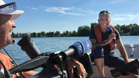 Andreas Hieke moderiert von einem Boot aus die Hessenschau