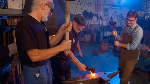 Moderator Dieter Voss (rechts) schwingt den Hammer in der Schmiede von Rüdiger Schwenk (Mitte) in Aarbergen