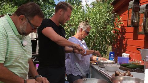Moderator Jens Pflüger (Mitte) zusammen mit den Gastgebern Jaromir und Gabi Kallus aus Raunheim bei der Zubereitung der Mahlzeit