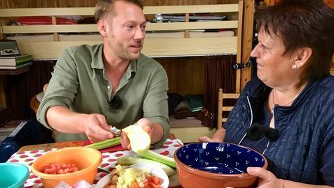 Moderator Jens Pflüger unterstützt Konny Rissmann bei der Zubereitung der Mahlzeit
