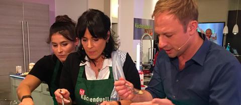 Vanessa Volland, Anke Volland und Tobi Kämmerer stehen in der Küche.