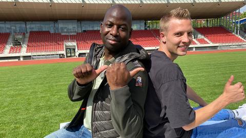 Coach Kelechi und Fußballer Steffen Friedrich sitzen im Stadion.