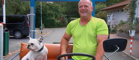 Camping-Chef Sven Bettermann sitzt zusammen mit Bulldogge Bernd in seinem Auto.
