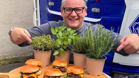 Klaus Breinig steht vor einem LKW und hat auf einem Brett mehrere Burger und Töpfe mit Kräutern.