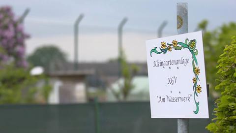 Das Schild einer Kleingartenanlage in Wiesbaden, im Hintergrund ist das Gelände des US-Militärstützpunktes zu sehen.
