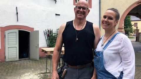 Axel und Nicole Friedersdorf stehen in Arbeitskleidung im Hof des Schlosses von Nidda.