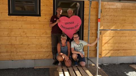"""Barbara und Werner Krupp stehen in der Tür ihres Hauses und halten ein Herz mit der Aufschrift """"Unser Traumprojekt""""."""
