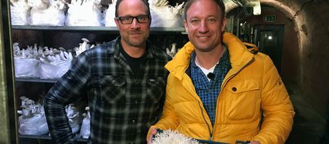 Moderator Tobias Kämmerer steht mit Mathias Kroll in einem Keller voller gezüchteter Pilze.