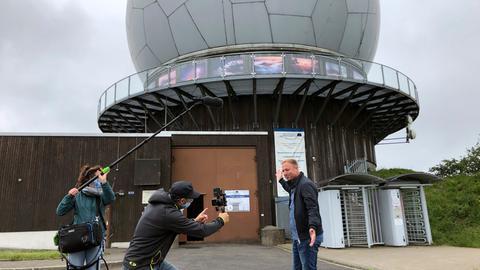 Tobias Kämmerer steht zusammen mit dem Kamerateam vor dem Radom auf der Wasserkuppe.