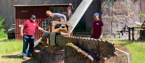 Tobias Kämmerer mit Reinhold Stock und Lothar Noll an der Kettensäge im Steinbruch Michelnau
