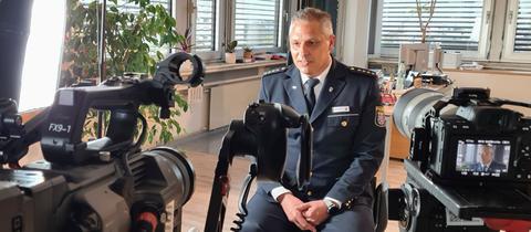 Der Leiter der Polizeidirektion Main-Kinzig, Jürgen Fehler sitz vor Kameras im hr-Interview.